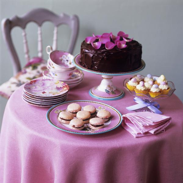 chocolate cake macarons and cupcakes on small table